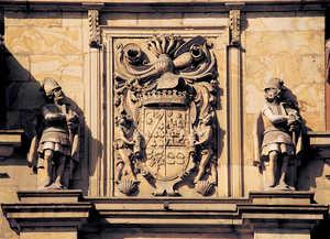 20.El escudo de armas de los Lazcano (1638), defendido por dos guerreros preside la entrada del palacio del Duque del Infantado (Lazkao). El palacio sustituye a las viejas torres medievales desde las que los Lazcano dominaban con puño de hierro a los labradores de la alcaldia de Areria.